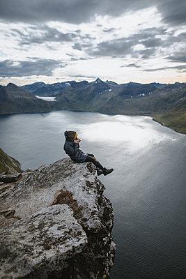 Norway, Senja, Man taking photo sitting on edge of steep cliff on top of mountainÊSegla - p1427m2174064 by Oleksii Karamanov