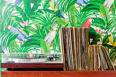 Record player and collection of records against wallpaper in jungle and parrots pattern - p300m2250974 by Javier De La Torre Sebastian