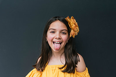 Close-up of girl wearing yellow headband sticking out tongue against black background - p300m2251095 by MORNINGVIEW AGENCY