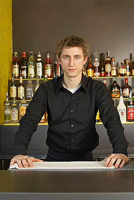 Portrait of young barman behind his bar - p4292306f by Bob Barkany