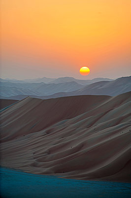 Middle East, Oman.  Dunes of  The Empty Quarter or Ar Rub al Khali at sunset. - p652m1576198 by John Warburton-Lee