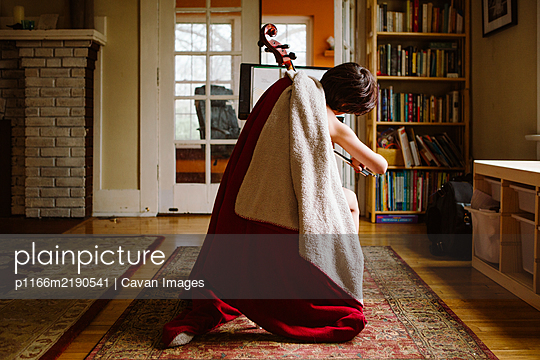 Rear view of a child wrapped in a red blanket practicing cello inside - p1166m2190541 by Cavan Images