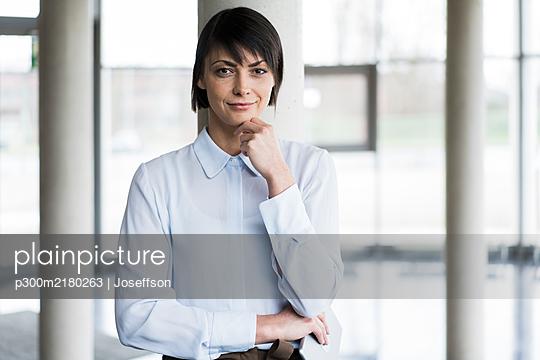 Serene businesswoman standing in bright office building - p300m2180263 by Joseffson