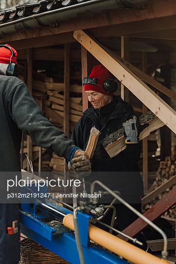 Senior couple using table saw - p312m2191247 by Jennifer Nilsson