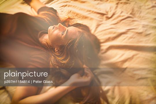 Weiblicher Teenager liegt auf einem Bett - p397m1154814 von Peter Glass