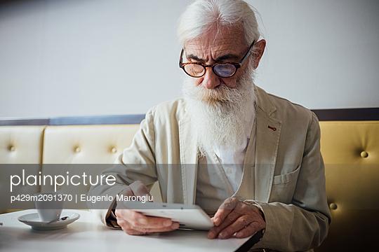 Senior businessman using digital tablet in cafe - p429m2091370 by Eugenio Marongiu