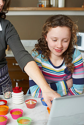Mother and daughter cooking in kitchen - p1023m806275f by Paul Viant