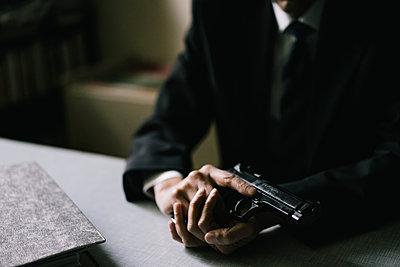 Mann im Anzug mit Handfeuerwaffe und Aktenordner - p1180m1171570 von chillagano