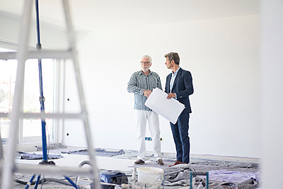 Man in suit and senior man talking on room under construction - p300m2004080 von Robijn Page