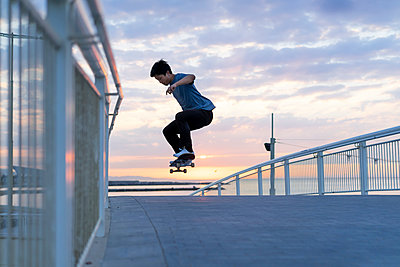 Young Chinese man skateboarding at sunsrise near the beach - p300m2012280 by VITTA GALLERY