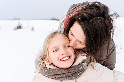 Close-up of mother kissing smiling daughter during winter - p300m2251529 by Ekaterina Yakunina