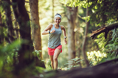 Excited female athlete running in forest - p300m2282416 by Mikel Taboada