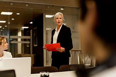 Businesswoman discussing with male and female colleagues in meeting at workplace - p426m2187205 by Maskot