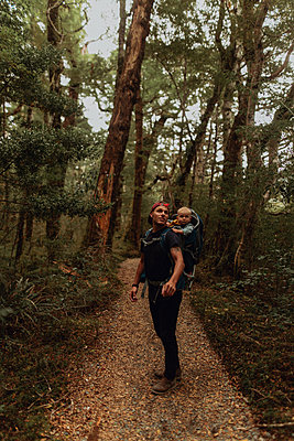 Hiker with baby exploring forest, Queenstown, Canterbury, New Zealand - p924m2098279 by Peter Amend