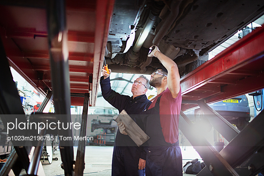 Male mechanics with flashlight working under car in auto repair shop - p1023m2196755 by Tom Merton