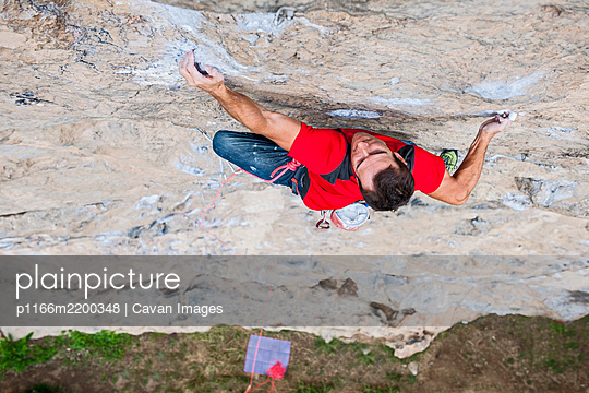 view from above of man climbing rock face in Yangshuo - p1166m2200348 by Cavan Images
