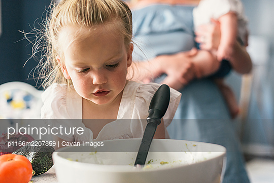 Toddler daughter looking at guacamole while mother and baby look on - p1166m2207859 by Cavan Images
