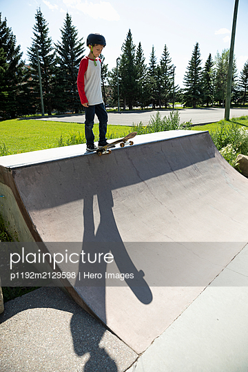 Boy with skateboard on ramp in sunny skate park - p1192m2129598 by Hero Images