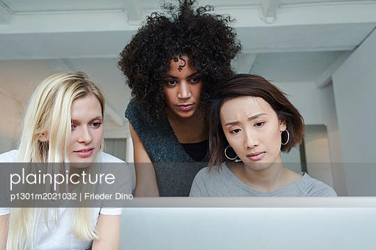 Drei junge, moderne Frauen besprechen kreative Idee am Laptop - p1301m2021032 von Delia Baum