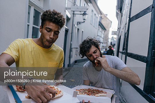 Two friends eating takeaway pizza in the city - p300m1536293 by Kniel Synnatzschke