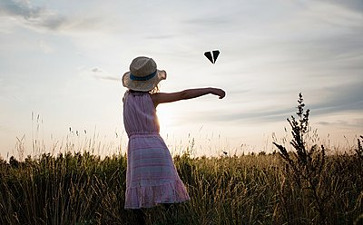 young girl playing with a paper plane in a meadow at sunset in summer - p1166m2137868 by Cavan Images