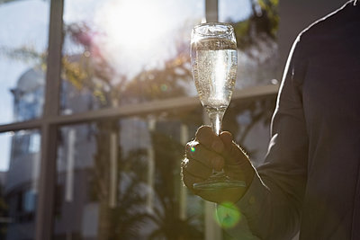 Close-up of man holding a glass of champagne - p1315m1186386 by Wavebreak