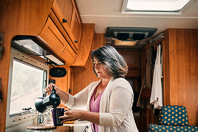 Mature woman pouring coffee in cup at motor home - p300m2299019 by LUPE RODRIGUEZ