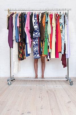 Frau hinter einem Kleiderständer - p427m1195143 von Ralf Mohr