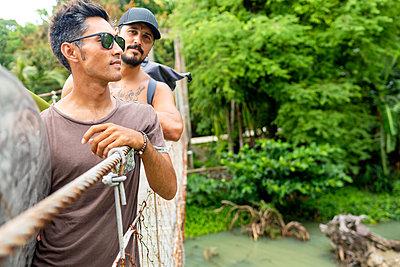Men on rope bridge, Pagudpud, Ilocos Norte, Philippines - p429m2075363 by dotdotred