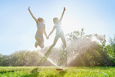 Caucasian girls jumping over backyard sprinkler - p555m1303574 by Chris Clor