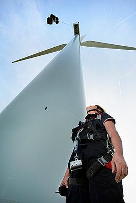 Low angle view of engineer looking up at wind turbine. Terneuzen, Zeeland, Netherlands, Europe - p924m1480614 by Mischa Keijser