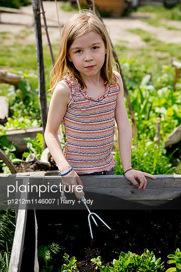 Mädchen arbeitet im Hochbeet - p1212m1146007 von harry + lidy