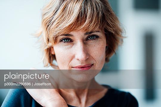 Businesswoman staring in office - p300m2290596 by Joseffson
