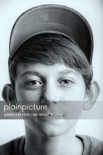 Close up of Caucasian teenage boy wearing baseball cap
