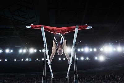 Male gymnast performing upside-down splits on parallel bars in arena - p1023m1217731 by Chris Ryan