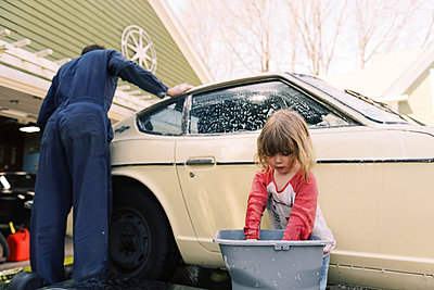 A father and his toddler daughter washing a classic car together. - p1166m2190666 by Cavan Images