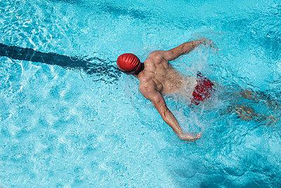 Young Caucasian male swimmer swimming butterfly stroke in swimming pool - p1315m2091039 by Wavebreak