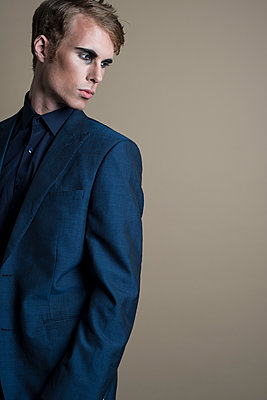 Young man wearing makeup in blue suit and dark shirt, looking over his shoulder. - p1433m1563448 by Wolf Kettler