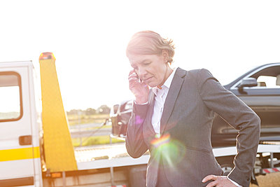 Businesswoman on cell phone having a car breakdown - p300m1018777f by Milton Brown