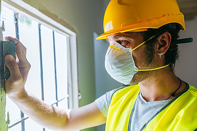 Close-up of worker sanding wooden window - p300m1588009 by Kiko Jimenez