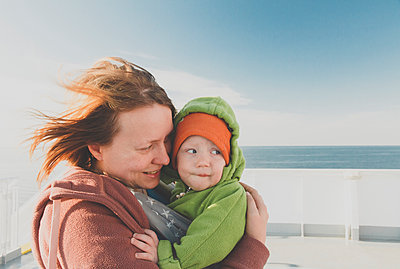 Mother carrying baby boy in a sling on a ferry - p300m2114446 by Irina Heß