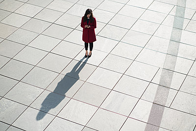 Businesswoman using smartphone and standing on concrete floor - p300m2154564 by Hernandez and Sorokina