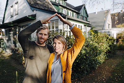 Portrait of smiling couple standing in front of their home - p300m2205526 by Kniel Synnatzschke