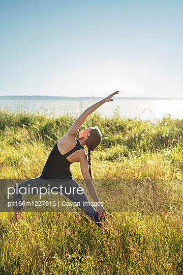 Woman practicing extended side angle pose yoga on grassy field by sea during sunny day - p1166m1227816 by Cavan Images