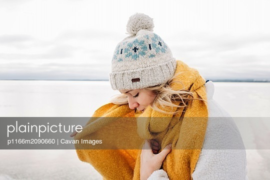 portrait of blonde woman wrapping up warm at the beach in winter - p1166m2090660 by Cavan Images