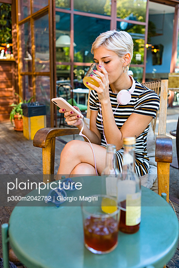 Young woman at pavement cafe enjoying soft drink while looking at smartphone - p300m2042782 von Giorgio Magini