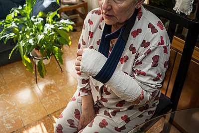 Caucasian adult woman with broken arm sitting at home - p1166m2246501 by Cavan Images