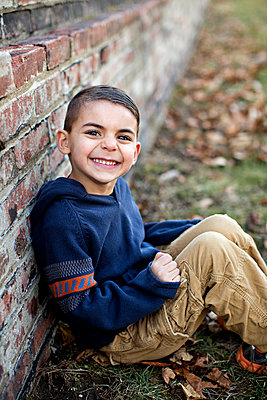 Boy leaning against stone wall - p1211m1045023 by Danny Weiss
