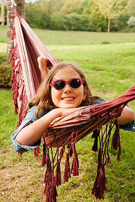 Portrait of smiling girl wearing sunglasses lying in hammock - p300m1587082 by Annie Hall
