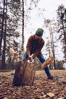 Young man chopping woog in the forest - p300m2059334 by CSSHOT